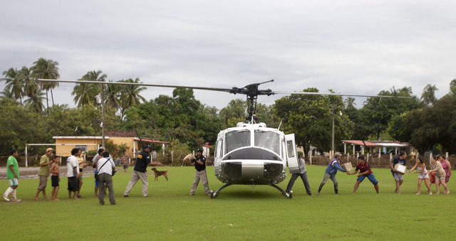 Residents of a community affected by the rains and floods caused by Tropical Storm Manuel unload aid from a helicopter in San Jeronimo, Mexico, Friday, Sept. 20, 2013. Federal police have been hel ...
