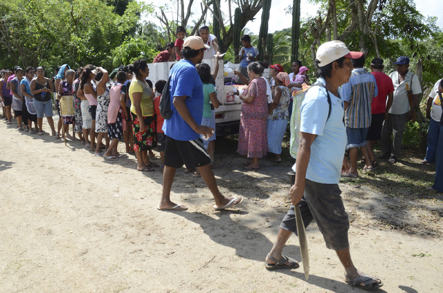 Villagers affected from the rains and floods caused by Tropical Storm Manuel line up to get a simple meal donated by residents of a nearby community, in the village of Salsipuedes, Mexico, Friday  ...