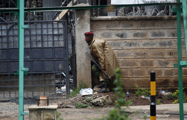 A Kenyan  security officer takes cover as gunfire and explosions are heard from the Westgate Mall in Nairobi, Kenya, on Monday. Multiple large blasts have rocked the mall where a hostage siege is  ...