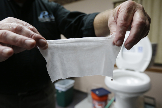 In this photograph taken, Friday, Sept. 20, 2013, in Middlesex, N.J., Rob Villee, executive director of the Plainfield Area Regional Sewer Authority in New Jersey, holds up a wipe he flushed throu ...