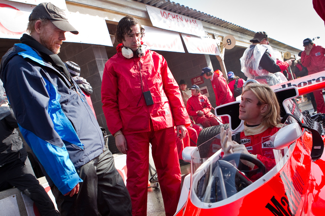 """This image released by Universal Pictures shows director Ron Howard, left, and Chris Hemsworth on the set of """"Rush.""""   The film, chronicling Formula One's 1976 world championship between ..."""