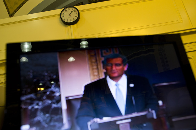 Sen. Ted Cruz, R-Texas, is seen on a television screen in the Senate Press Gallery during the 10th hour of his speech on the Senate floor on Wednesday. Cruz began a lengthy speech urging his colle ...