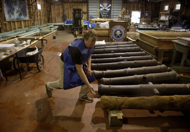 Chris Macort, a field archeologist working with the Whydah pirate ship museum, reaches down to check one of the ships cannons at the museum's warehouse in Brewster, Mass., Tuesday, Sept. 17, 2013. ...
