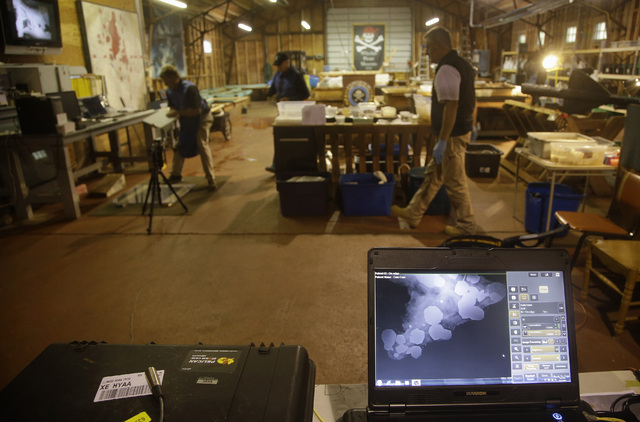 An X-ray of a concretion, front,  a rocky mass that forms when metals such as gold and silver chemically react to salt water, is seen on a laptop computer at the Whydah pirate ship museum's wareho ...