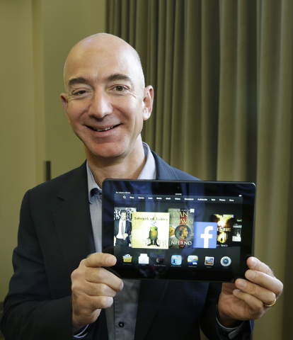 Jeff Bezos, CEO of Amazon.com, poses for a photo Tuesday, Sept. 24, 2013, with the 8.9-inch version of the new Amazon Kindle HDX tablet computer in Seattle. Amazon has refreshed its line-up of tab ...