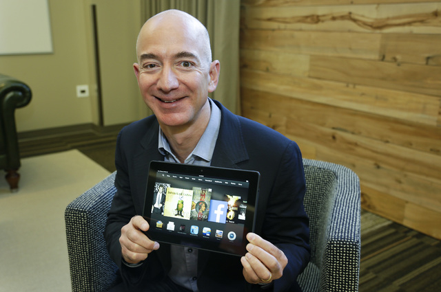 Jeff Bezos, CEO of Amazon.com, poses for a photo Tuesday, Sept. 24, 2013, with the 8.9-inch version of the new Amazon Kindle HDX tablet computer in Seattle. Amazon has refreshed its lineup of tabl ...