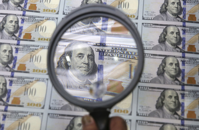 A sheet of uncut $100 bills is inspected during the printing process at the Bureau of Engraving and Printing Western Currency Facility in Fort Worth, Texas, Tuesday, Sept. 24, 2013.  The federal p ...
