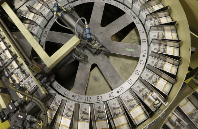 Just cut stacks of $100 bills make their way down the line at the Bureau of Engraving and Printing Western Currency Facility in Fort Worth, Texas, Tuesday, Sept. 24, 2013.   (AP Photo/LM Otero)