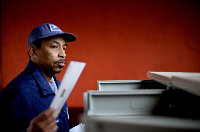 FILE - In this Thursday, Feb.  7, 2013, file photo, U.S. Postal Service letter carrier, Michael McDonald delivers mail, in Atlanta. The financially struggling Postal Service is seeking a 3-cent in ...
