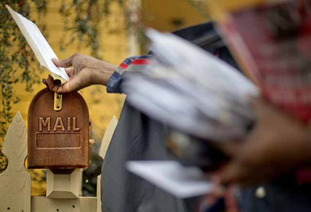 FILE - In this Thursday, Feb.  7, 2013, file photo, U.S. Postal Service letter carrier, Jamesa Euler, delivers mail, in Atlanta. The financially struggling Postal Service is seeking a 3-cent incre ...
