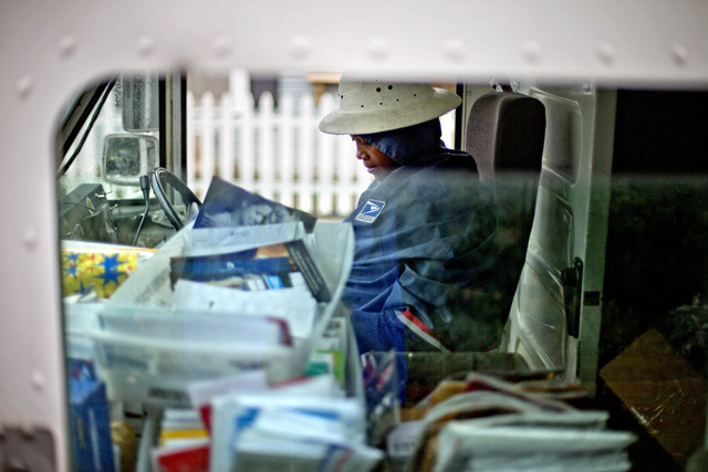 FILE - In this Thursday, Feb.  7, 2013, file photo, U.S. Postal Service letter carrier, Jamesa Euler, delivers mail, in Atlanta. The financially struggling Postal Service said Wednesday, Sept. 25, ...
