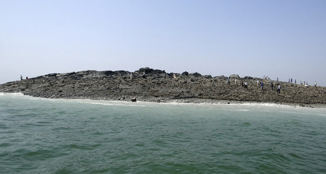 In this photo released by the Gwadar local government office on Wednesday, Sept 25, 2013, people walk on an island that reportedly emerged off the Gwadar coastline in the Arabian Sea. A deadly mag ...