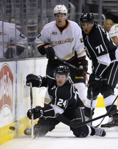 Los Angeles Kings center Colin Fraser, below, passes the puck from his knees as Anaheim Ducks defenseman Hampus Lindholm, upper left, and center Jordan Nolan watch during the first period of an NH ...