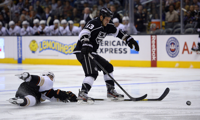 Los Angeles Kings left wing Kyle Clifford, right, takes the puck as Anaheim Ducks defenseman Ben Lovejoy reaches in during the second period of their NHL preseason hockey game, Tuesday, Sept. 24,  ...