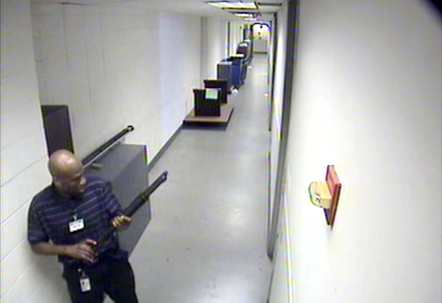This image from video provided by the FBI, shows Aaron Alexis moves through the hallways of Building #197 at the Washington Navy Yard on Sept. 16 in Washington, carrying a Remington 870 shotgun. A ...