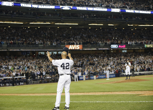 New York Yankees relief pitcher Mariano Rivera (42) tips his cap to the crowd in a curtain call after pitching in the eighth and ninth innings in a baseball game against the Tampa Bay Rays in his  ...
