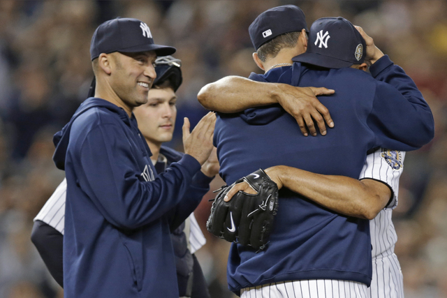 New York Yankees' Derek Jeter, left, applauds as retiring Yankees pitcher Andy Pettitte, back to camera, embraces relief pitcher Mariano Rivera in the ninth inning of Rivera's final appearance at  ...