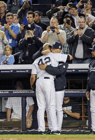 New York Yankees manager Joe Girardi hugs pitcher Mariano Rivera (42) during the ninth inning of a baseball game against the Tampa Bay Rays on Thursday, Sept. 26, 2013, at Yankee Stadium in New Yo ...