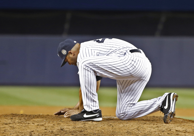 New York Yankees relief pitcher Mariano Rivera gathers dirt from the mound after his final appearance in a baseball game at Yankee Stadium, Thursday, Sept. 26, 2013, in New York. The Yankees defea ...