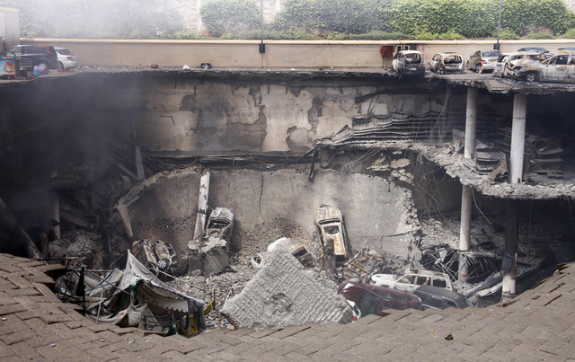 This photo released by the Kenya Presidency shows the collapsed upper car park of the Westgate Mall in Nairobi, Kenya Thursday, Sept. 26, 2013. Working near bodies crushed by rubble in a bullet-sc ...