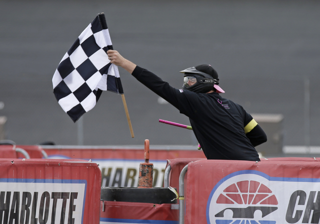 NASCAR driver Kyle Busch grabs the checkered flag during a paintball game against members of the media at Charlotte Motor Speedway in Concord, N.C., Tuesday, Sept. 24, 2013, promoting the upcoming ...