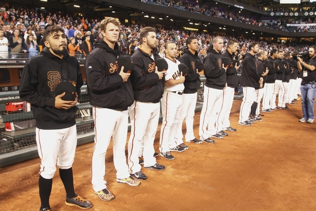 San Francisco Giants observe a moment of silence before a baseball game aganist the Los Angeles Dodgers, Thursday, Sept. 26, 2013, in San Francisco, in memory of a man who was fatally stabbed afte ...