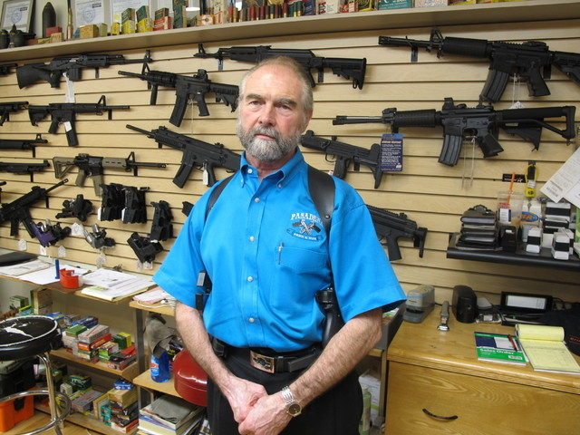 Frank Loane, owner of Pasadena Pawn and Gun, stands in front of a wall of assault rifles at his store in Pasadena, Md., on Thursday, Sept. 26, 2013. Loane, who said he has seen significant boost i ...