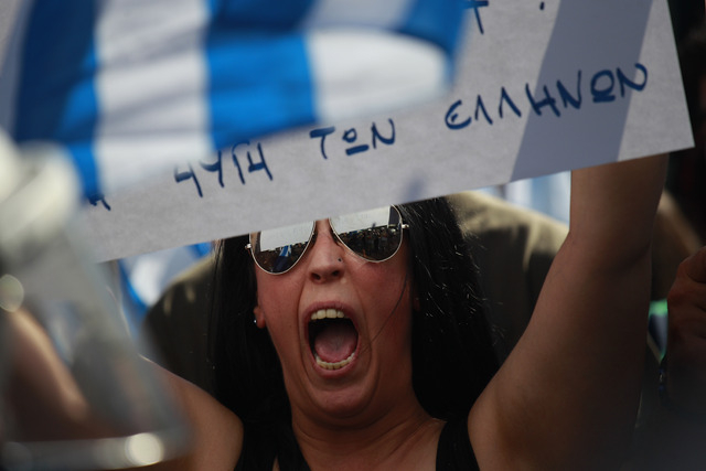 "A supporter of the extreme far-right Golden Dawn party holds a partially seen placard that reads: ""Listen Chief, Listen again, you have ridiculed the system one more time - Golden Dawn of the Gree ..."