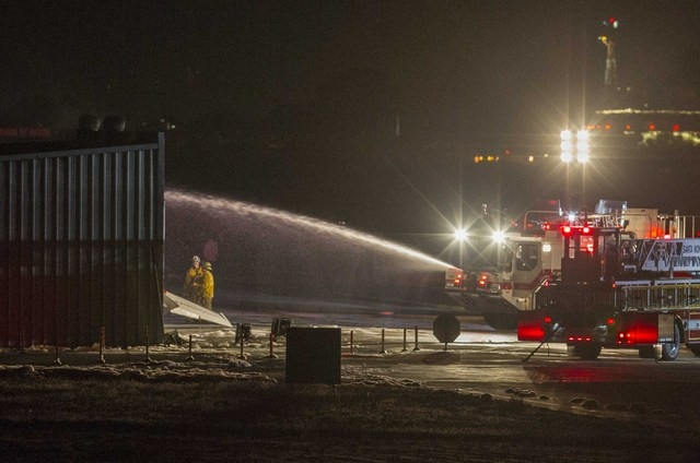 Firefighters work to extinguish fire at the site of a plane crash in Santa Monica, Calif., on Sunday night. Authorities say a twin-jet Cessna Citation went off the right side of the runway and cra ...