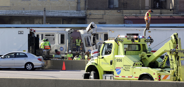 Authorities inspect the wreckage of two Chicago Transit Authority trains that crashed Monday, Sept. 30, 2013, in Forest Park, Ill. The crash happened when a westbound train stopped at the CTA Blue ...