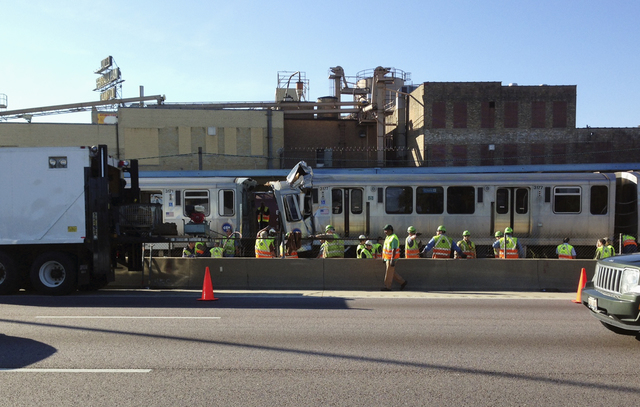 Emergency personnel work at the scene where two Chicago Transit Authority trains collided during rush hour Monday, Sept. 30, 2013, in Forest Park, Ill. About four dozen people were injured in the  ...
