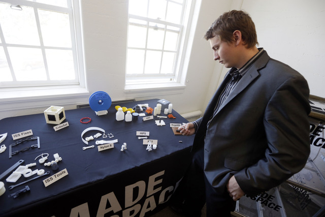 Aaron Kemmer, CEO and co-founder of Made in Space, looks through some items made with the company's 3D printer which will eventually be used in space on Monday, Sept. 16, 2013, in Mountain View, C ...