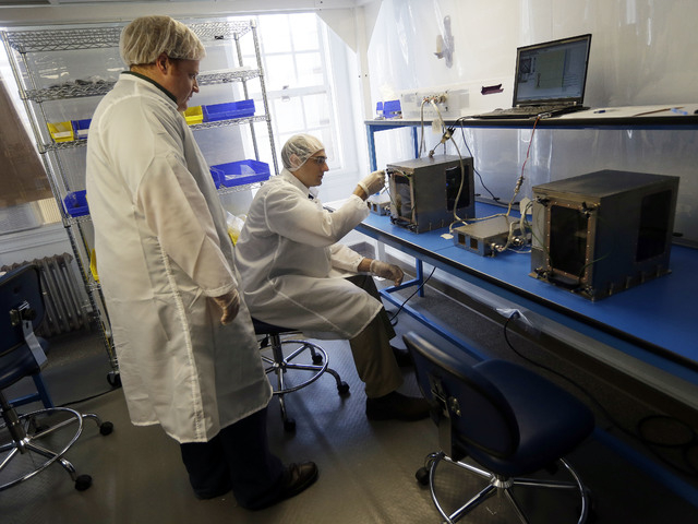 Project manager Matthew Napoli, left, and director of research and development Michael Snyder test a 3D printer which will eventually be used in space on Monday, Sept. 16, 2013, at Made in Space i ...