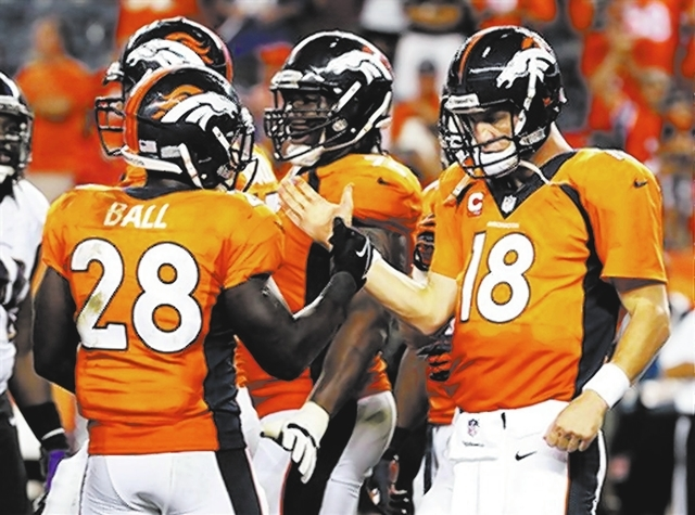 JOE MAHONEY/THE ASSOCIATED PRESS Broncos quarterback Peyton Manning (18), greeting running back Montee Ball after Denver's 49-27 victory over the Ravens on Thursday, passed for seven touchdo ...