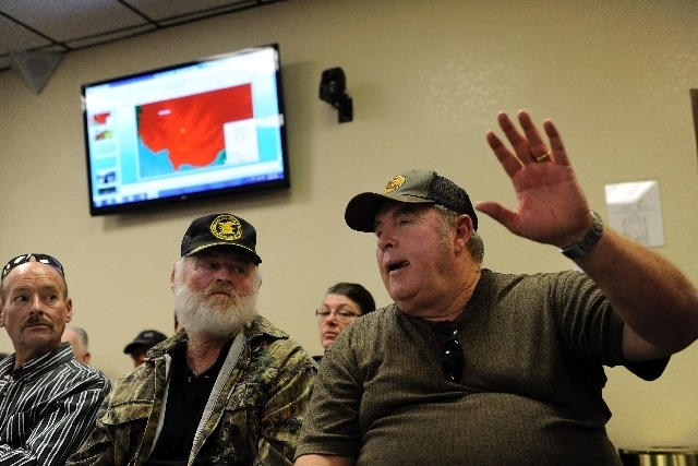 Trout Canyon resident Dennis Walker, right, raises his hand to ask a question during a town-hall style meeting at the Southern Nevada Health District offices last month. Residents met with county, ...