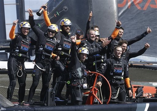 Oracle Team USA crew, including skipper Jimmy Spithill, second from left, and tactician Ben Ainslie, front center, celebrate after winning the 19th race against Emirates Team New Zealand to win th ...