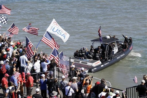 Oracle Team USA members wave at supporters as they are ferried to their catamaran before the 19th race of the America's Cup sailing event against Emirates Team New Zealand on Wednesday, Sept. 25,  ...