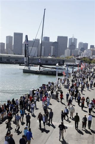 Fans walk along the waterfront before the start of 19th race of the America's Cup sailing event  between Emirates Team New Zealand and Oracle Team USA on Wednesday, Sept. 25, 2013, in San Francisc ...