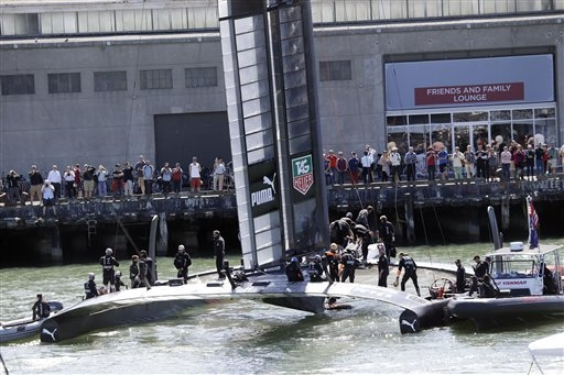 Oracle Team USA members board their catamaran as fans watch before the 19th race of the America's Cup sailing event against Emirates Team New Zealand on Wednesday, Sept. 25, 2013, in San Francisco ...