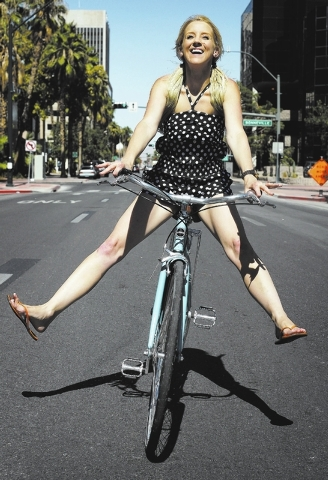 Owner Amie Pellegrini poses for a portrait while riding down the middle of 4th street in front of her newly opened shop The Town Bike at the Juhl condo building in Las Vegas on Sept. 17, 2013. (Ja ...