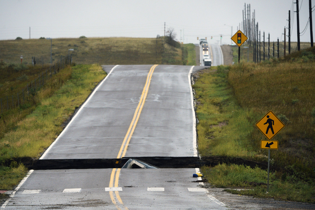 ADDS MORE PRECISE LOCATION INFORMATION- A road is collapsed following flooding at Highway 287 and Dillon at the Broomfield/Lafayette border, Colo., sending three vehicles into the water on Thursda ...