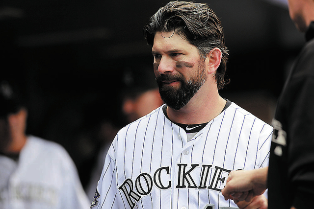 Colorado Rockies first baseman Todd Helton heads to field to face the Arizona Diamondbacks in the first inning of a baseball game in Denver on Sunday, Sept. 22, 2013. (AP Photo/David Zalubowski)
