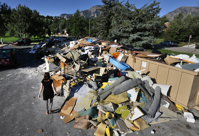 A woman looks for reclaimable wood from a heap of household flooring, furniture and other items destroyed by flooding the previous week, in Boulder, Colo., Friday Sept. 20, 2013. The flood recover ...
