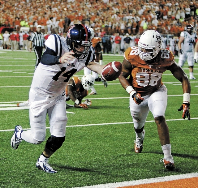 Ole Miss quarterback Bo Wallace (14) scores a touchdown against Texas' Cedric Reed (88) during the third quarter of an NCAA college football game Saturday Sept. 14, 2013, in Austin, Texas. (AP Pho ...
