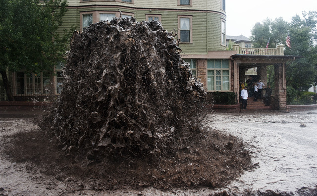 A geyser of flood water shoots out of a sewer on Canon Avenue next to the Cliff House in Manitou Springs, Colo. Thursday, Sept. 12, 2013 as storms continue to dump rain over the Waldo Canyon burn  ...