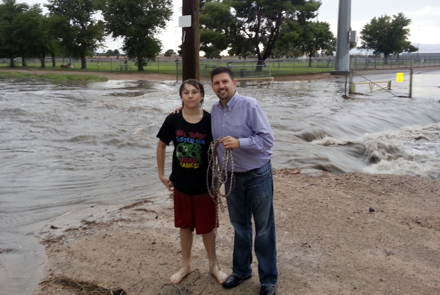 This Sept. 11, 2013 image shows Nevada state Sen. Mark Manendo and a boy he rescued, known only as Anthony, posing at the site of the rescue in Las Vegas. Manendo says he was photographing a wash  ...