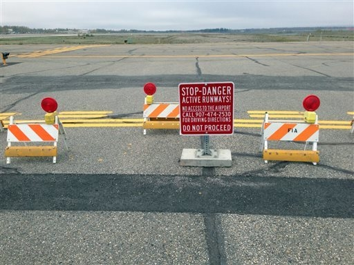 This Sept. 20, 2013 image provided by the Fairbanks International Airport shows the barricaded entrance to a taxiway, at Float Pond Road blocking access to Taxiway B in Fairbanks, Alaska. A glitch ...
