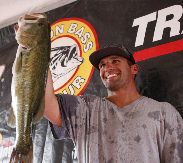 Professional angler Michael Caruso, of Phoenix, displays one of his fish after having his catch weighed at Callville Bay Marina on Lake Mead during the NITRO Mercury WON Bass U.S. Open bass fishin ...