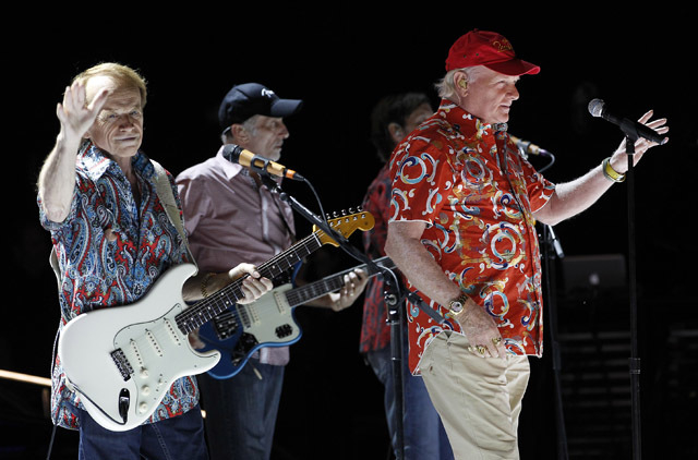 The Beach Boys' Al Jardine, left, and Mike Love, right, wave to the crowd as David Marks starts playing the first song during the opening show of their 50th Anniversary tour kickoff Tuesday, April ...
