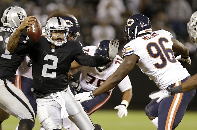 Oakland Raiders quarterback Terrelle Pryor (2) avoids Chicago Bears defensive end Kyle Moore (96) on his 25-yard touchdown run during the third quarter of an NFL preseason football game in Oakland ...